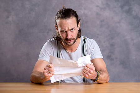 tearing: young man is annoyed about a letter