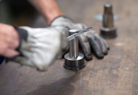 workpiece: workers hand measuring a metal workpiece Stock Photo