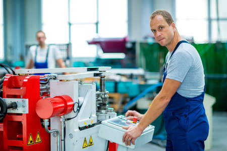 young worker in factory using machine Stock Photo