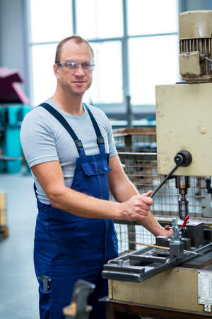 jobholder: young worker in factory using drill machine