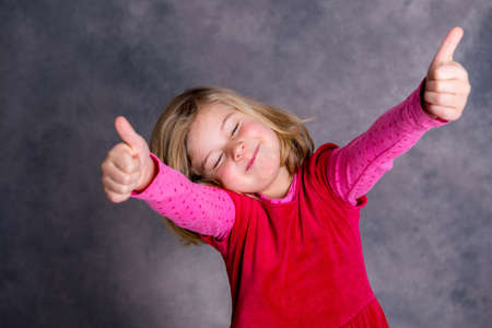jubilating: funny girl with thumbs up in front of gray background Stock Photo