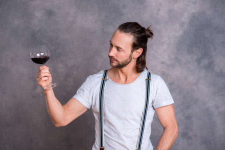 skoal: young man in front of gray background drinking red wine