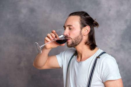 La vera storia di Ricciardo di Chinzica, giudice in Pisa. 52224543-giovane-uomo-di-fronte-a-sfondo-grigio-bere-vino-rosso