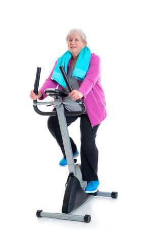 perspiring: gray-haired female senior train with fitness machine Stock Photo
