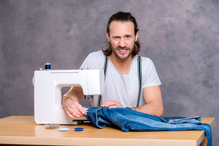tailor tape: young tailor with sewing machine in front of gray background Stock Photo