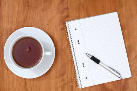 scratchpad: notepad with pen and a cup of tea on wooden table from above