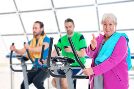 female senior and two young men in fitness center