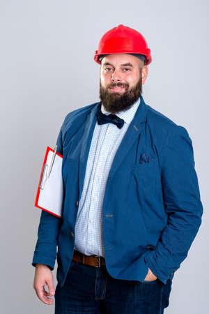 casco rojo: retrato de un joven arquitecto con el casco rojo y el portapapeles Foto de archivo