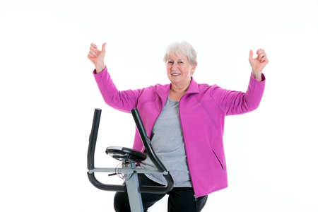 arms up: gray-haired female senior with arms up train with fitness machine