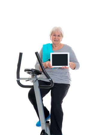 sports programme: gray-haired female senior train with fitness machine and using tablet PC