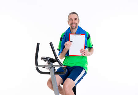 sports programme: young man with clipboard train on fitness machine