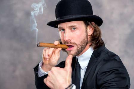 bowler hat: young businessman with bowler hat and thumb up smoking big cigar Stock Photo