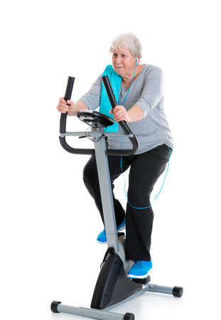 grey haired: gray-haired female senior train with fitness machine Stock Photo