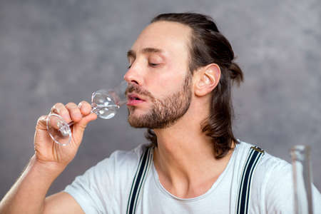booze: young man in front of gray background drinking clear spirit