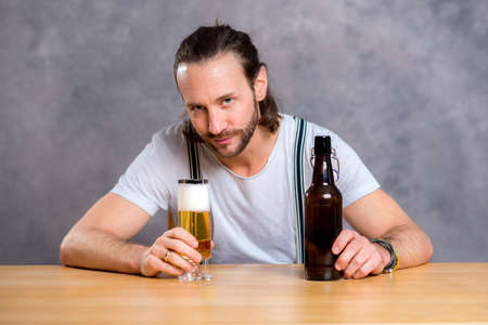 skoal: young man in front of gray background drinking beer