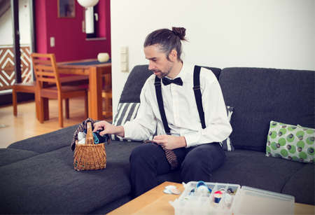 mending: young bearded man in white shirt with bow-tie mending sox Stock Photo