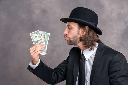 bowler hat: young businessman with bowler hat in black suit showing money