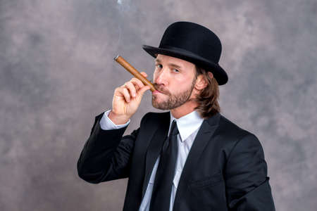 bowler hat: young businessman with bowler hat in black suit smoking big cigar