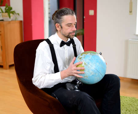 terrestrial globe: young bearded man in white shirt with bow-tie with  terrestrial globe