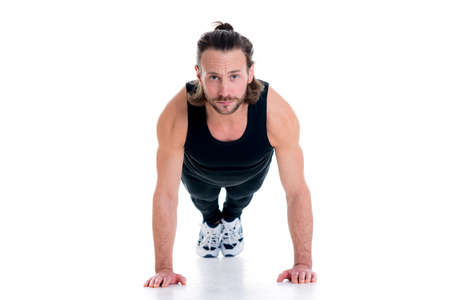 fitnesscenter: young man doing press-up in front of white background
