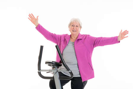 exultation: gray-haired female senior with arms up train with fitness machine