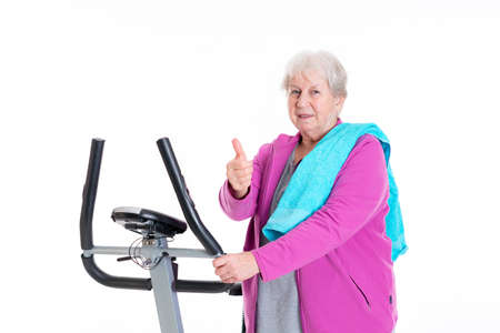 fitnesscenter: gray-haired female senior with thumb up train with fitness machine