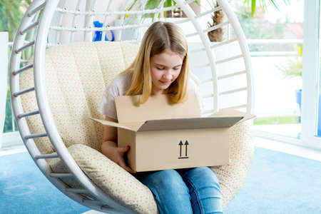 delivery room: blond girl sitting in chair and opening a package
