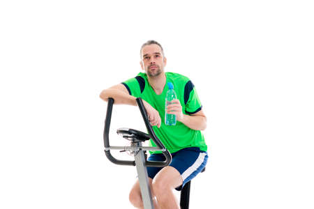 fitnesscenter: young man in green shirt with water bottle train with fitness machine
