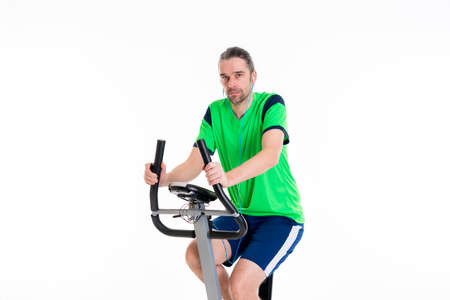 fitnesscenter: young man in green shirt train with fitness machine and listening music