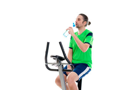 fitnesscenter: young man in green shirt train with fitness machine and drinking water