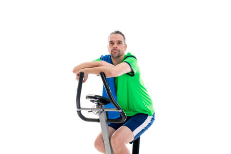 fitnesscenter: young man in green shirt train with fitness machine