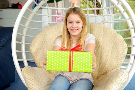 mothering: blond girl with green gift box in a chair