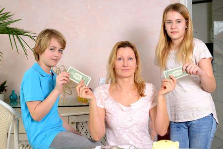 money pocket: rubia de la madre que da a su dinero de bolsillo ni�os