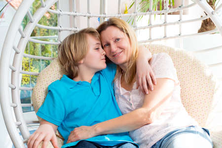 hugged: blond mother hugged her son at home
