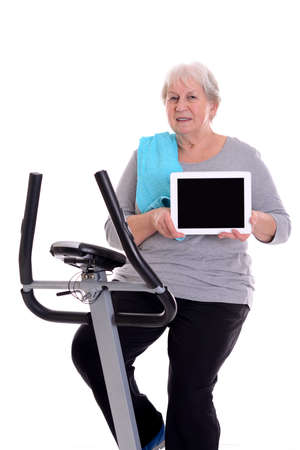 fitnesscenter: gray-haired female senior train with fitness machine and showing tablet PC Stock Photo