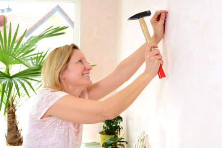 redecorate: blond woman redecorate home and working with hammer