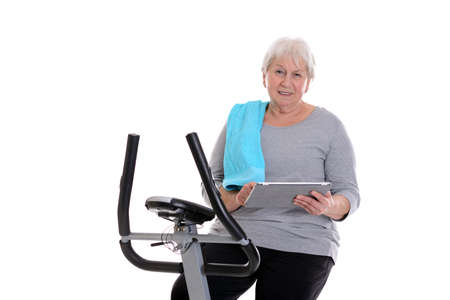 fitnesscenter: gray-haired female senior train with fitness machine and using tablet PC