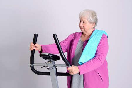 fitnesscenter: gray-haired female senior train with fitness machine Stock Photo