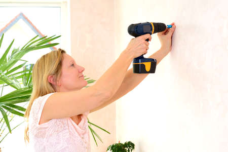 redecorate: blond woman redecorate home and working with cordless screwdriver