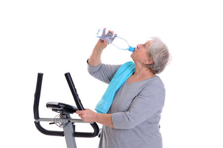 fitnesscenter: gray-haired female senior train with fitness machine and drinking water