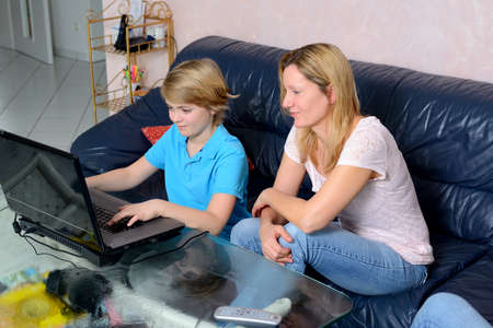 blond mother and her son using computer together