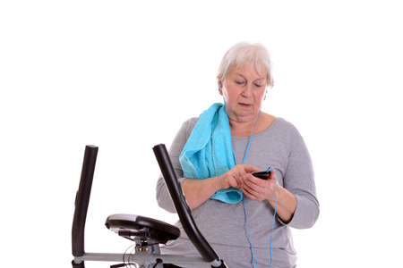 fitnesscenter: gray-haired female senior train with fitness machine and using phone Stock Photo