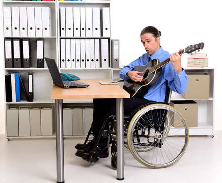 paraplegico: disablet business man in wheelchair playing the guitar