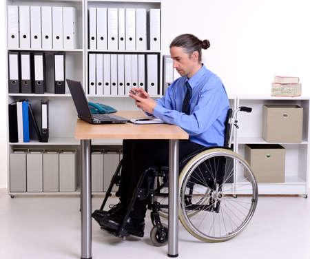 paraplegic: hombre de negocios disablet en silla de ruedas con su tel�fono inteligente Foto de archivo
