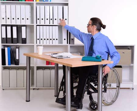paraplegico: disablet business man in wheelchair taking a folder Foto de archivo