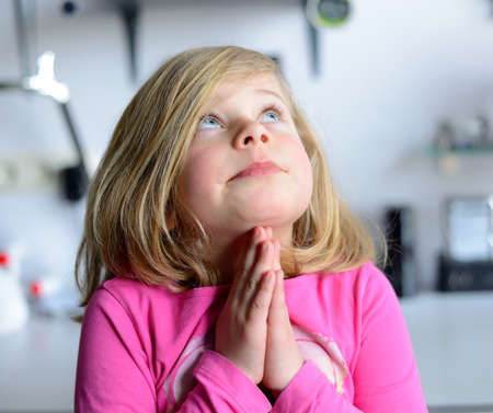 smile please: little girl in pink dress is praying Stock Photo