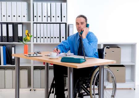 paraplegico: hombre de negocios en silla de ruedas disablet est� llamando