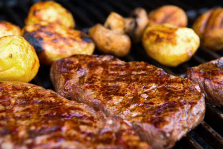 rump steak: delicious grilled rump steak with mushrooms and potatoes on barbecue