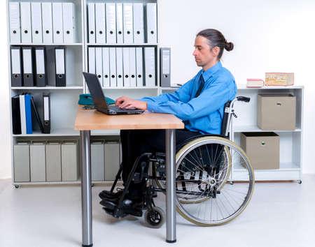 paraplegic: disabled business man in wheelchair working with the computer Foto de archivo