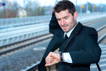 railroad station: businessman in suit on railroad station in hastiness